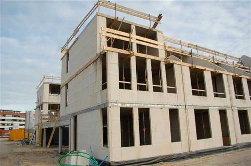 The 18 households that buy the properties in the two back-to-back terraces work together to hire one contractor to build the basic structure of their homes and the shared garage between the two terraces. This saves them money and speeds up delivery