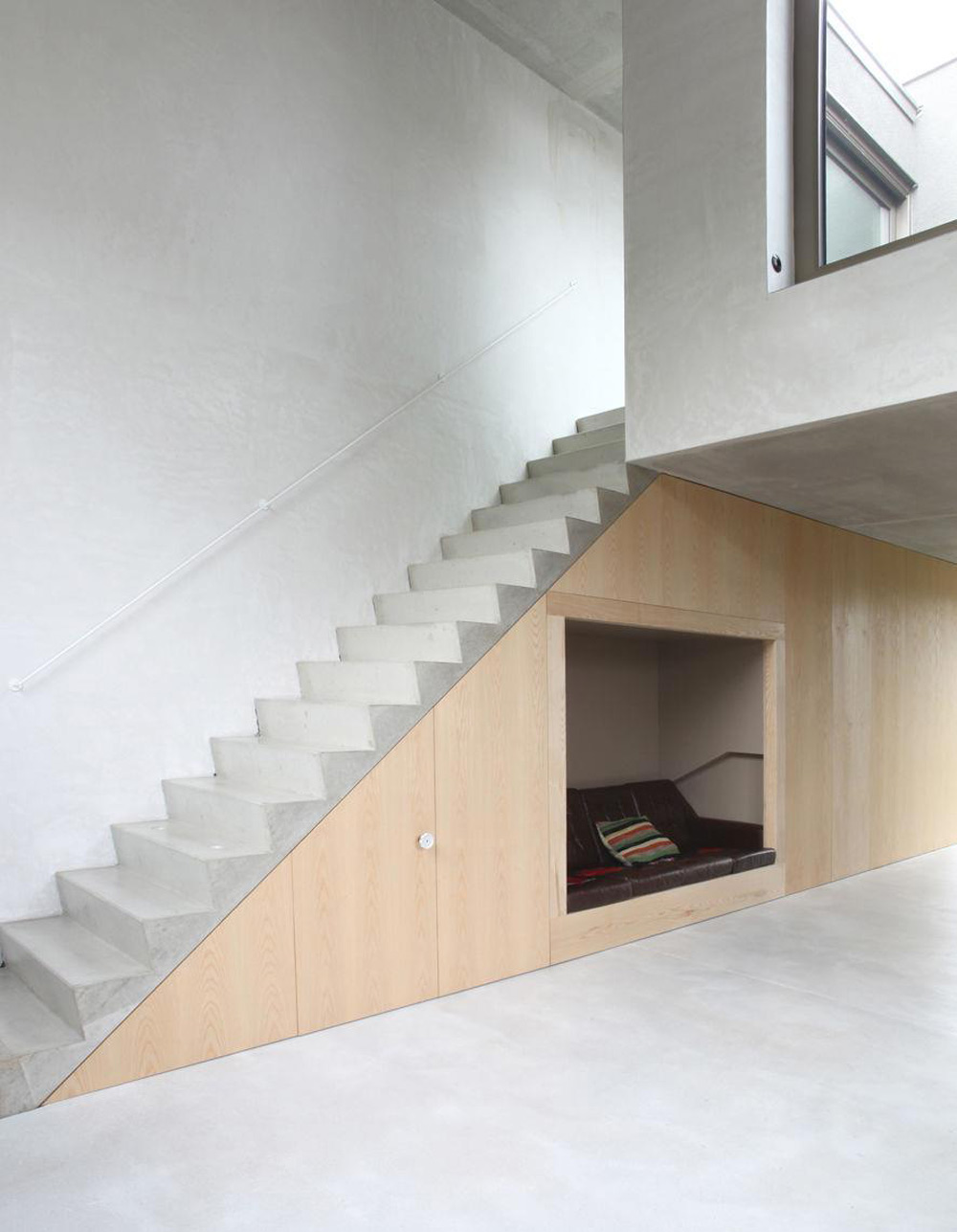 The staircase is located in the same position in each house; some owners have retained the concrete wall and ceiling finishes, other have plastered the walls and painted them
