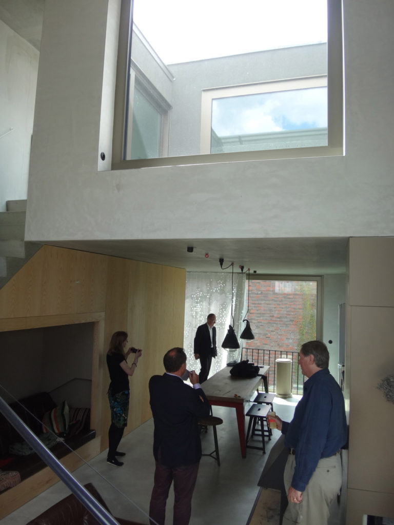 An upper level dining/kitchen space, partially double height, opening onto a roof terrace/deck above